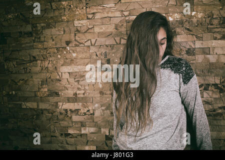 Sad teenage girl hair covering face - Stock Photo