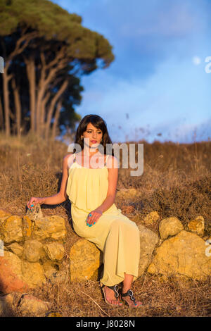 Lonely young woman wearing a yellow summer dres sat on the rocks outdoors thinking