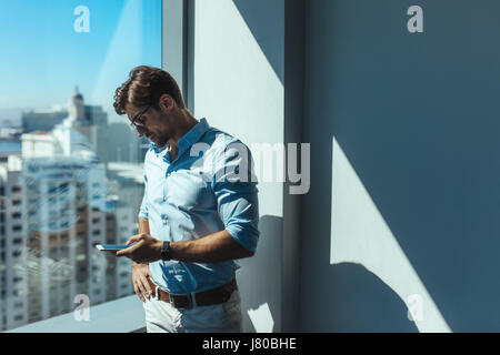 Young businessman looking at mobile phone standing beside a window. Man dressed in formals standing near window - Stock Photo