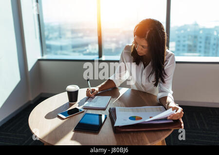 Young woman entrepreneur making business working at coffee table in office. Female business executive making business - Stock Photo