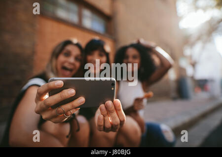 Three female friends making selfie with mobile phone. Group of women sitting outdoors and taking self portrait with - Stock Photo