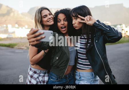 Happy female friends making selfie with smart phone. Multi ethnic group of women hanging out in the city and taking - Stock Photo