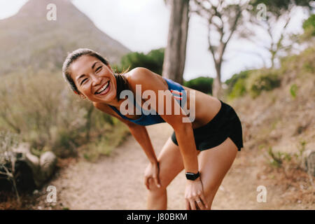 Healthy young woman standing on mountain trail with her hands on knees and laughing. Asian female runner in sportswear taking a break after running wo