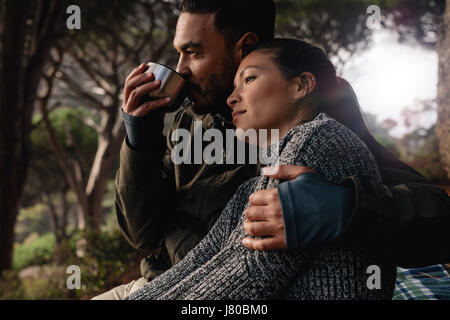 Young man and woman sitting outdoors. Relaxed young couple resting outdoors with man drinking coffee. - Stock Photo