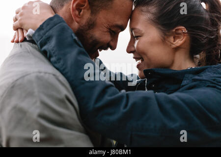 Close-up side portrait of a young couple in love to looking each other lovingly and leaning their heads on each - Stock Photo