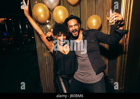 Couple smiling and dancing, having fun during disco party. Happy man and woman enjoying party at nightclub. - Stock Photo