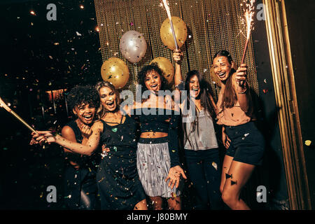 Shot of group of girls in the nightclub having a great time. Group of female friends partying in pub. - Stock Photo