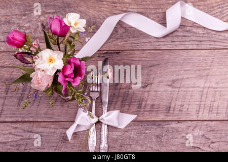 Place table settings with fork and knife, tied with a white satin ribbon, and flowers on an vintage table top view, - Stock Photo