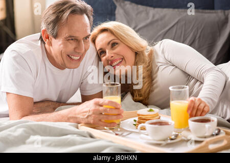 Happy middle aged couple having breakfast together in bed - Stock Photo