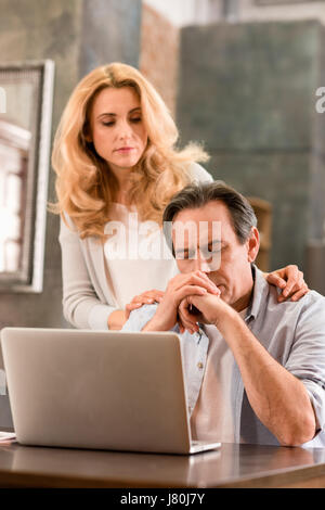 Blonde middle aged woman looking at upset husband using laptop at home - Stock Photo