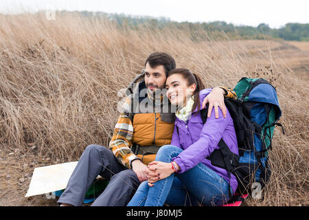 Happy young couple with backpacks sitting embracing on dry grass and looking away - Stock Photo