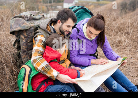 Young family with backpacks sitting on grass and looking at map in countryside at autumn day - Stock Photo