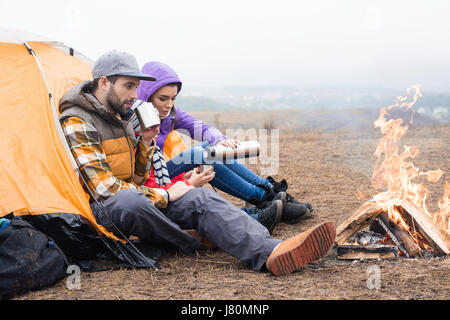 Family with one child sitting near tent and drinking hot tea from thermos while resting near burning fire in countryside - Stock Photo