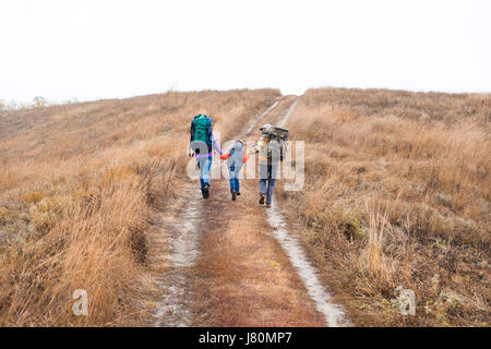 Back view of happy young family with backpacks holding hands and running on rural path at cloudy autumn day - Stock Photo