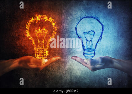 Two human hands holding flaming and splashing light bulbs on a gray background. Thinking exchange and idea partnership - Stock Photo