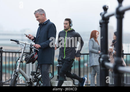 Businessman with bicycle texting with cell phone and male runner on urban ramp - Stock Photo