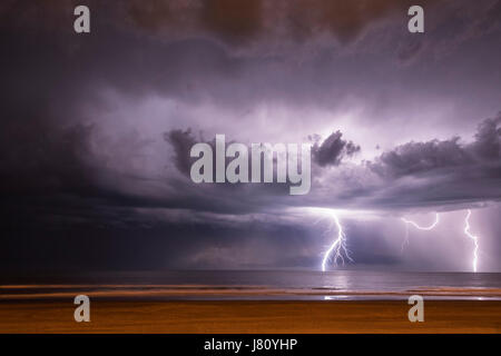 Lightning on the sea from the beach in Claromeco, Buenos Aires, Argentina - Stock Photo