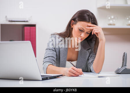 Young businesswoman is working in her office. - Stock Photo