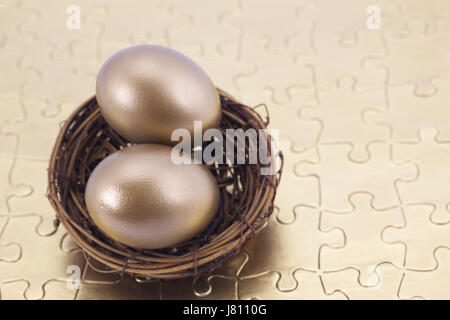 Two gold eggs in nest placed on puzzle show rewards of building a strong, retirement portfolio built on solid investment - Stock Photo