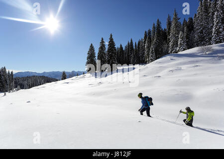 Mother and Son hiking in snow on the Pokljuka plateau, Slovenia. - Stock Photo