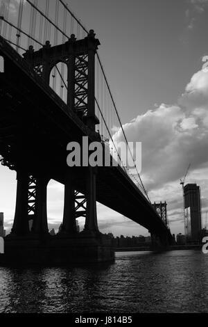 View across the East River with silhouettes of the supporting pier legs of the Manhattan Bridge from DUMBO in Brooklyn, - Stock Photo