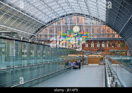 England, London, St Pancras railway station on Euston Road, man with suitcase sits on concourse awaiting his train. - Stock Photo