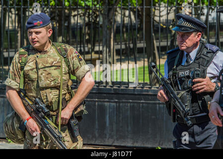 Whitehall, London, UK. 25th May, 2017. Soldiers, of the household cavalry and armed police guard the Houses of Parliament - Stock Photo