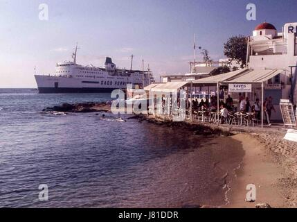 Chora, Mykonos, Greece. 3rd Oct, 2004. A ferry passes busy cafes lining the bay in Mykonos. Tourism is a major industry - Stock Photo