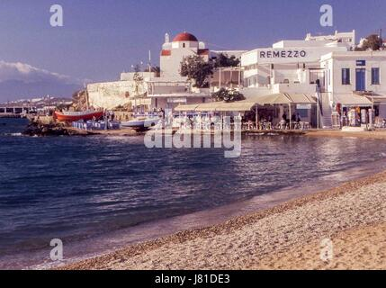 Chora, Mykonos, Greece. 3rd Oct, 2004. Busy cafes line the bay in Mykonos. Tourism is a major industry and Mykonos - Stock Photo