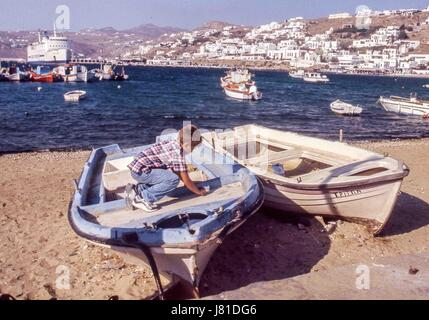 Chora, Mykonos, Greece. 3rd Oct, 2004. A young boy plays on a beached boat in the busy, picturesque old harbor of - Stock Photo