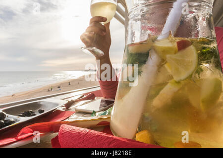 Jug of white sangria with woman hand behind with the beautiful light of the sunset on the beach - Stock Photo