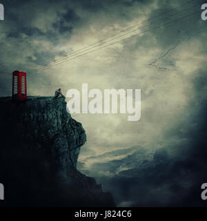 Surreal view as a sad, young man, standing on the edge of a cliff near a red telephone box, waiting someone to call - Stock Photo