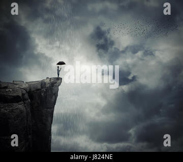 Man with an umbrella stand on the edge of the cliff, calling the rain. Mysterious place above the clouds. - Stock Photo