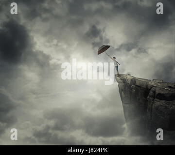 Boy trying to catch his umbrella on the edge of a cliff above the clouds. Escape and fly away. - Stock Photo