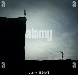 Conceptual image with two lost persons standing on a cliff at different hights, trying to find each other. Parallel - Stock Photo
