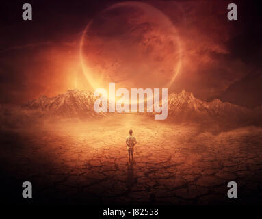 Surreal background as a young boy walks on another planet with dry and cracked ground, following a shining space - Stock Photo
