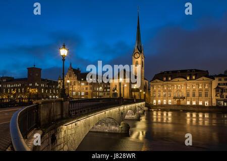 Illuminated Fraumunster Church and River Limmat in Zurich, Switzerland - Stock Photo