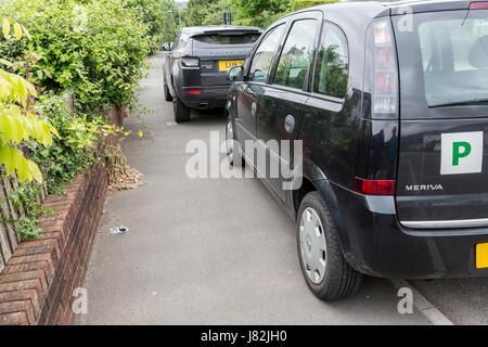 Cars parked on pavement obstructing pedestrian access, Wales, UK - Stock Photo