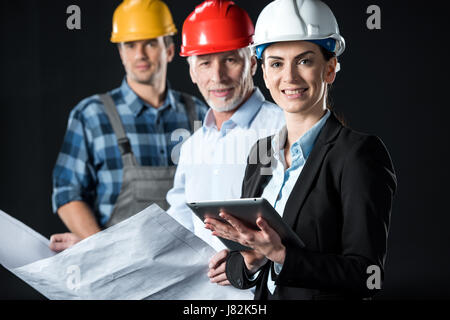 Two architects with digital tablet and blueprint and engineer looking at camera and smiling - Stock Photo