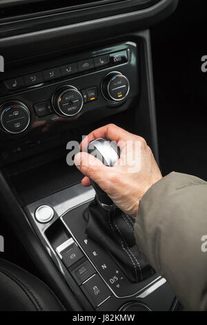 Drivers hand holds gear lever of modern luxury crossover car. Close-up photo with selective focus - Stock Photo