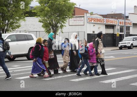 Muslim women dressed in traditional dress with children walking home after school in the Kensington neighborhood - Stock Photo