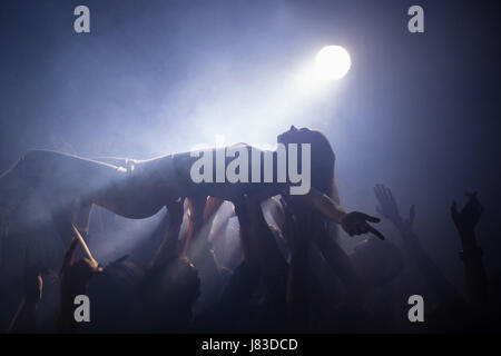 Crowd surfing at a concert in nightclub - Stock Photo