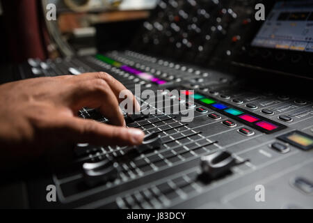 Hand of male audio engineer using sound mixer in recording studio - Stock Photo