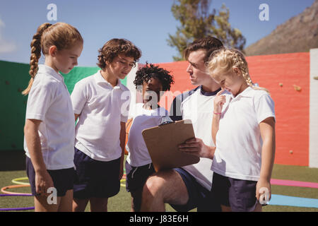 Coach and schoolkids discussing on clipboard in schoolyard - Stock Photo