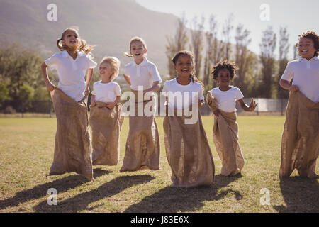 Schoolgirls having fun during sack race in park on a sunny day - Stock Photo