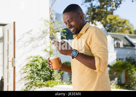 Happy young man using smartphone while holding disposable coffee cup at cafe - Stock Photo