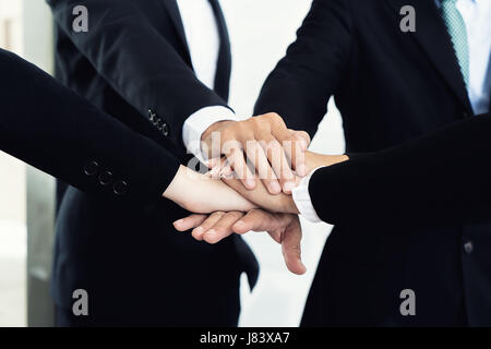Close up of business partners making pile of hands at meeting. Business people collaboration teamwork union concept. - Stock Photo