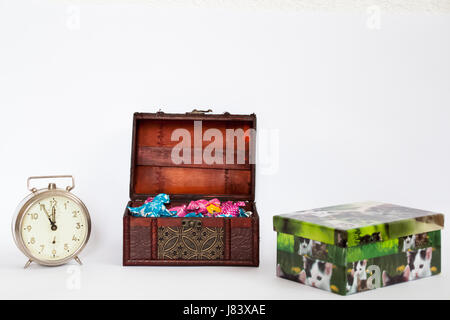 Tresure box full of colorful bonbons with a clock showing the last five minutes and a present box with pictures - Stock Photo