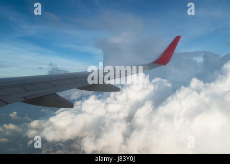 Wing of an airplane flying above the clouds. people looks at the sky from the window of the plane, using airtransport - Stock Photo