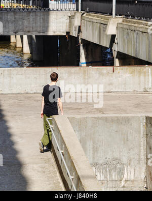Young man walking on the pier. Parkour in the urban space. Sports in the city. Sport activity. - Stock Photo